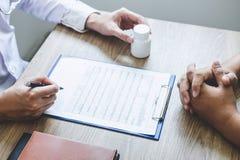 De professionele arts in witte eenvormige togalaag en het geduldige bespreken raadpleegt aan behandeling van symptoomziekte en he royalty-vrije stock fotografie