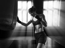 De professionele atleet leidt een slag aan de zak in de gymnastiek op stock foto's