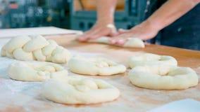 De professionele bakker vormt stukken van deeg in bakkerij commerciële keuken stock foto
