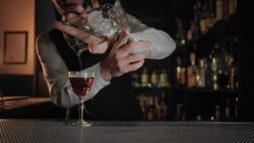 De professionele barman bij dark aangestoken bar bereidt drank voor stock videobeelden