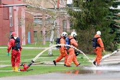De professionele brandbestrijders in oranje vuurvaste kostuums in witte helmen met gasmaskers testen brandslangen en brandkanonne stock foto