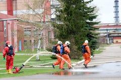 De professionele brandbestrijders in oranje vuurvaste kostuums in witte helmen met gasmaskers testen brandslangen en brandkanonne stock foto's