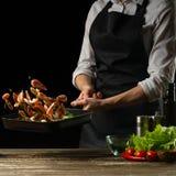 De professionele chef-kok bereidt een salade van verse garnalen, en groenten op een donkere achtergrond voor, die in motie bevrie stock foto's
