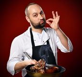 De professionele chef-kok toont Yummy teken en toont een pan met een juist voorbereid vlees op keuken van het restaurant aan royalty-vrije stock fotografie