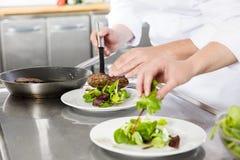 De professionele chef-koks bereidt lapje vleesschotels bij restaurant voor stock foto