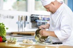 De professionele chef-koks maakt voedselschotels in grote keuken stock foto