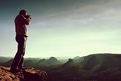 De professionele fotograaf neemt foto's met spiegelcamera op klip van rots Dromerig nevelig landschap, hete Zon hierboven Royalty-vrije Stock Afbeeldingen