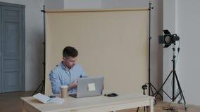 De professionele Fotograafwerken in foto's bewerken App op zijn Personal computer Gelukkige mens die beelden en horloge retoucher stock video
