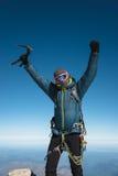De professionele gidswandelaar bij de bovenkant van de rots met zijn handen omhoog is tevreden met de volgende overwinning van he Stock Afbeeldingen