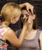 De professionele grimeur maakt oogmake-up op een cliëntgezicht de industrie van de schoonheidsmanier stock foto