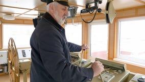 De professionele hogere kapitein in stuurhut stelt het schip in werking gebruikend twee hefbomen stock footage