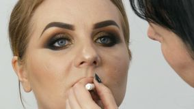 De professionele hoofdmake-upkunstenaar past donkerrode lippenstift op de model dunne lippen met speciale borstel en rokerige sam stock videobeelden