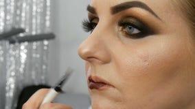 De professionele hoofdmake-upkunstenaar past donkerrode lippenstift op de model dunne lippen met speciale borstel en rokerige sam stock video