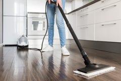 De professionele huis schoonmakende dienst De vrouw wast de vloer met een stoomzwabber stock afbeelding