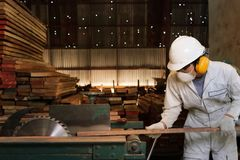 De professionele jonge werknemer die in wit eenvormig en veiligheidsmateriaal een stuk van hout op lijst snijden zag machine in t stock foto