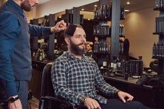 De professionele kapper gebruikt een borstel, bijna gebeëindigd kapsel royalty-vrije stock foto's