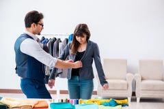De professionele kleermaker die metingen voor formeel kostuum nemen stock afbeelding