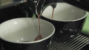 De professionele koffiemachine maakt koffie in twee zwart-witte mokken in een koffie het gieten van hete koffiedrank in de kop Wi stock footage