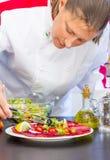 De professionele kok bereidt een plaat met salami en verse salade voor Royalty-vrije Stock Afbeeldingen