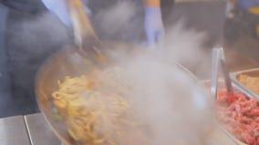 De professionele kok braadt noedels met groenten en vlees bij het festival van het straatvoedsel Beweeg gebraden gerecht met rund stock videobeelden