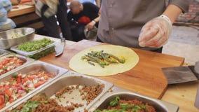 De professionele kok maakt taco met pitabroodje en groenten bij het festival van het straatvoedsel Proces om dicht omhoog te koke stock footage