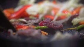 De professionele kok mengt bradend groenten en vlees stock videobeelden