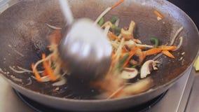 De professionele kok mengt groenten en paddestoelen in een pan bij het festival van het straatvoedsel, close-up stock video