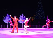 De professionele man en vrouwencijferschaatsers die bij Kerstmis op ijs presteren tonen op Internationaal Aandrijvingsgebied stock afbeelding