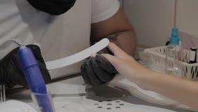 De professionele manicuremens poetst en maakt de spijkers van het meisje met een nagelvijl op glad stock video