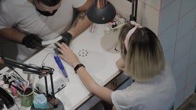 De professionele manicuremens poetst en maakt de spijkers van het meisje met een nagelvijl op glad stock footage