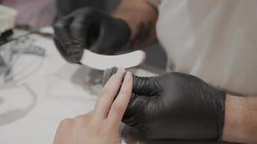 De professionele manicuremens poetst en maakt de spijkers van het meisje met een nagelvijl op glad stock videobeelden