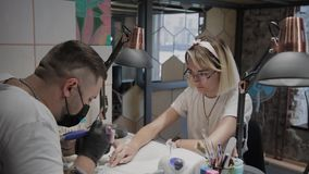 De professionele manicuremens verwijdert oud nagellak uit een meisje gebruikend een speciaal middel om nagellak te verwijderen stock videobeelden