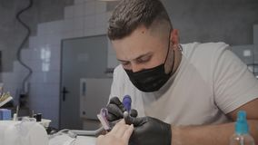 De professionele manicuremens verwijdert oud nagellak uit een meisje gebruikend een speciaal middel om nagellak te verwijderen stock video