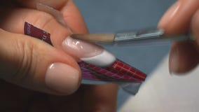 De professionele manicurewerken aangaande spijker van cliënt in schoonheidszaal Sluit omhoog stock footage