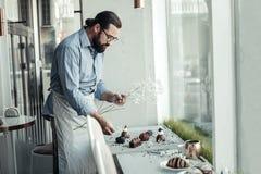 De professionele mannelijke bakker die van Nice de schotel verfraaien royalty-vrije stock afbeelding