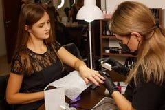 De professionele meester van manicure maakt tot de spijkers aan de cliënt stock fotografie