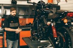 De professionele motowerktuigkundige heft een motorfiets op de lift op royalty-vrije stock fotografie