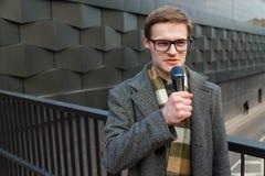 De professionele nieuwsverslaggever in oogglazen met microfoon zendt op de straat uit Manier of bedrijfsnieuws royalty-vrije stock afbeelding