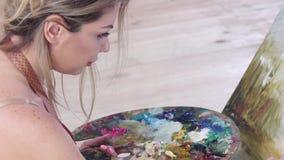 De professionele olieverven van de meisjeskunstenaar op canvas Details, zijaanzicht stock footage