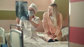 De professionele röntgenstraal van de artsenholding en het spreken aan jonge vrouwelijke geduldige zitting op bed stock footage