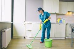 De professionele reinigingsmachine wast vloer met groene zwabber THeere is emmer naast haar Het meisje draagt eenvormig Zij houdt stock afbeelding