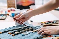 De professionele schilder die van de kunstenaarsuitrusting borstel kiezen stock foto