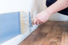 De professionele schildersarbeider schildert één muur Royalty-vrije Stock Foto's