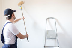 De professionele schildersarbeider schildert muur stock fotografie