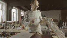 De professionele schrijnwerker perforeert gaten in houten raad door boor checking stock videobeelden
