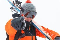 De professionele skiëratleet in een oranje zwart kostuum met een zwart skimasker met skis op zijn schouder richt aan de camera royalty-vrije stock fotografie