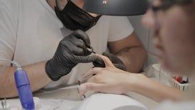De professionele vernissen van de manicuremens de spijkers van een meisje stock videobeelden