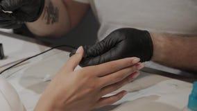 De professionele vernissen van de manicuremens de spijkers van een meisje stock footage