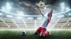 De professionele voetballer viert het winnen van het open stadion De voetballer houdt een trofee Medaille op de hals E stock foto's