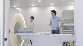 De professionele vrouw controleert de MRI-scanner tijdens diagnostiek stock video